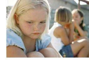 Menina esxcluída, sozinha, enquanto outras crianças brincam.
