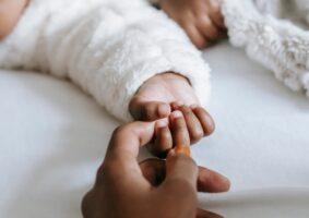 A idealização da maternidade perfeita e o peso do capacitismo. A foto mostra a mão de uma mãe, segurando a mãzinha de seu bebê. Ambos são pretos.