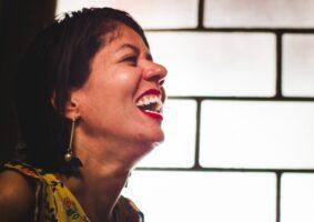 Dia Nacional da pessoa com deficiência. Fatine Oliveira, mestre em Comunicação Social e integrante do Grupo Afetos - Grupo de Pesquisa em Comunicação, Acessibilidade e Vulnerabilidades, UFMG, está de perefil, cabeça levemente levantada e sorriso contagiante. Ela é morena e tem cabelos curtos. Fatine é feminista e pessoa com deficência.