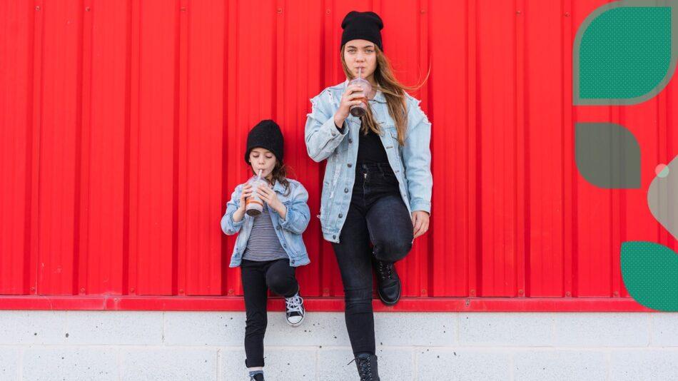 Para ilustrar o texto Empatia no Autismo, a imagem de uma moça e uma criança, vestidas iguais, encostadas numa parede, na mesma posição e tomando um suco.
